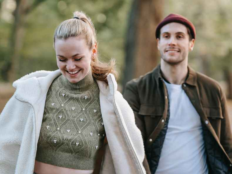 positive couple walking in park