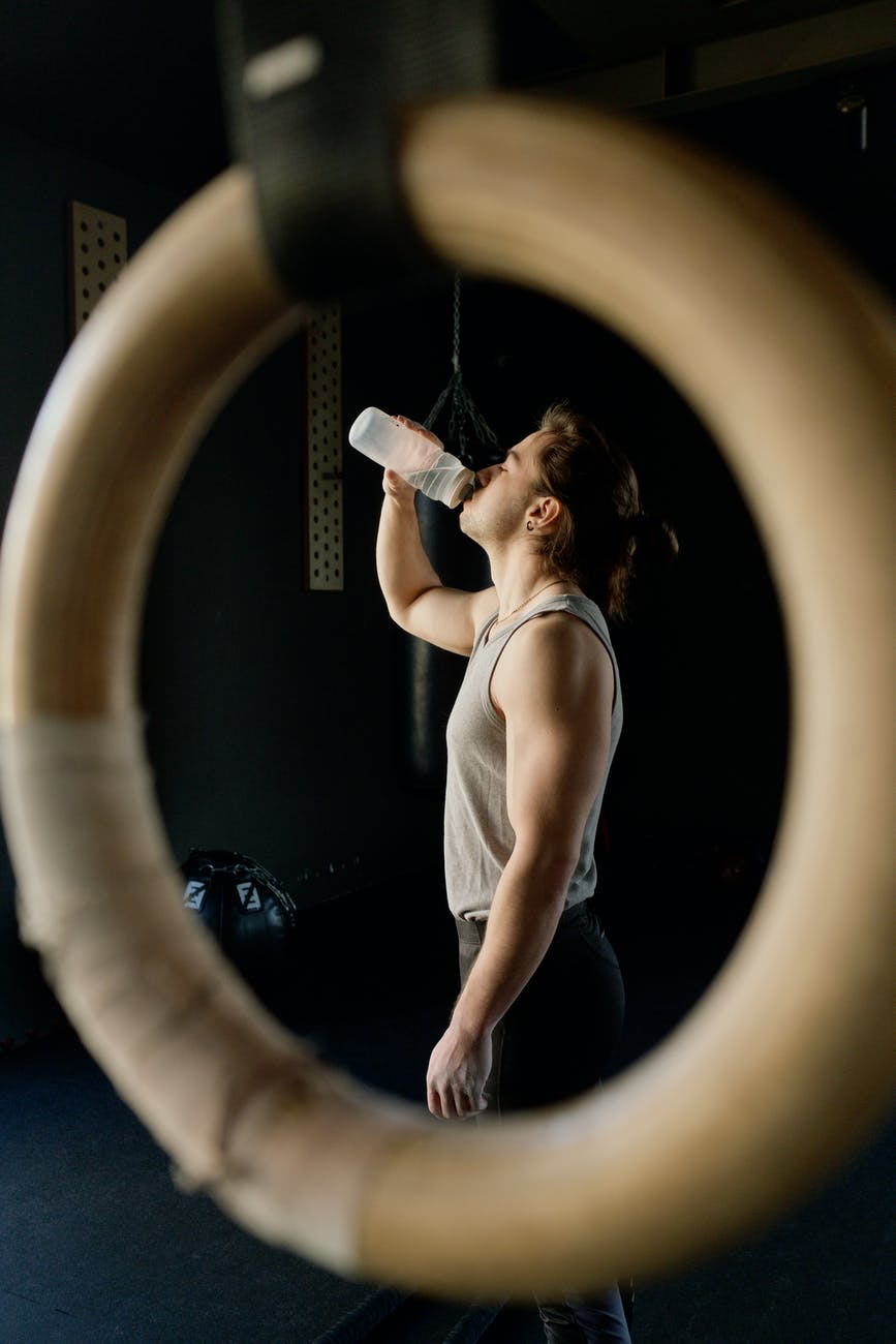 man drinking from bottle. Photo by Ivan Samkov on Pexels.com