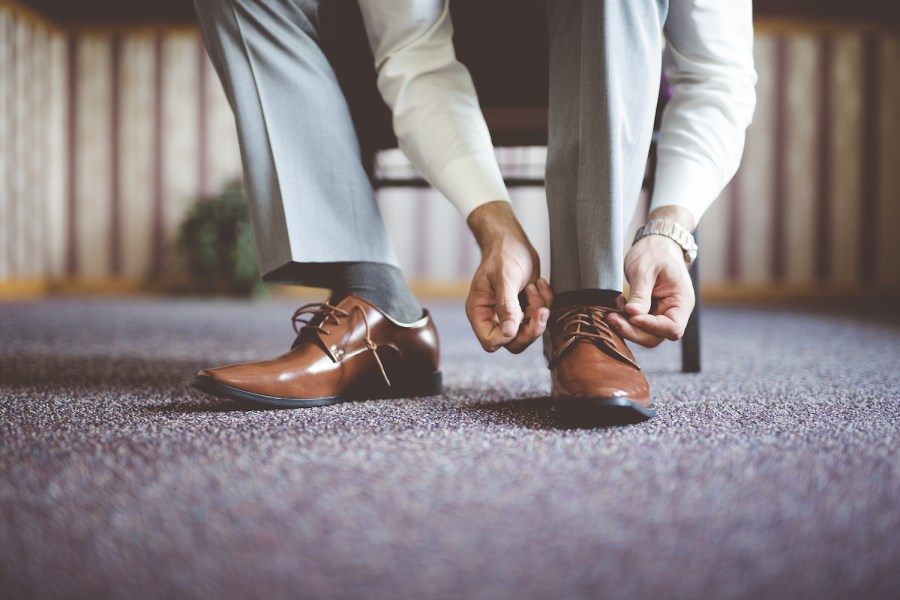 4 Timeless Men Styling Tips To Make Your Presence Felt O'clock. A closeup shot of a male tying his shoes and getting ready for a business meeting