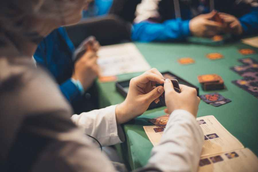 crop people playing cards at table