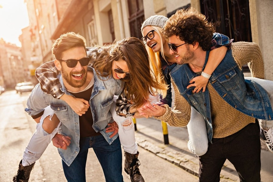 Picture of four friends having great time piggyback riding in the city. The men are carrying the women and the couples are wearing jeans jacket, checkered shirt, hat , glasses and jeans shirt. They are in a great mood laughing and smiling, walking in a small street without traffic between nice old houses.