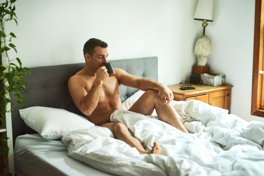 Shot of a young handsome shirtless man drinking coffee and chilling in bed at home.