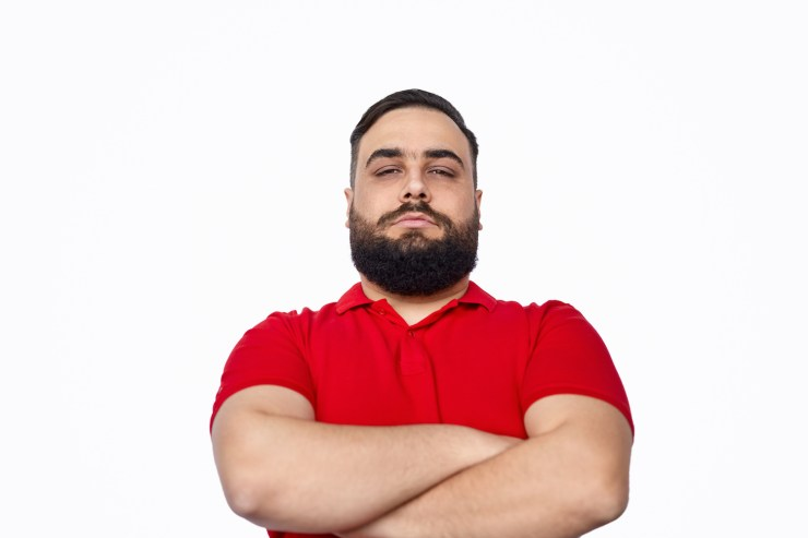 Overweight bearded ethnic guy with crossed arms looking at camera with serious face expression while standing against white background