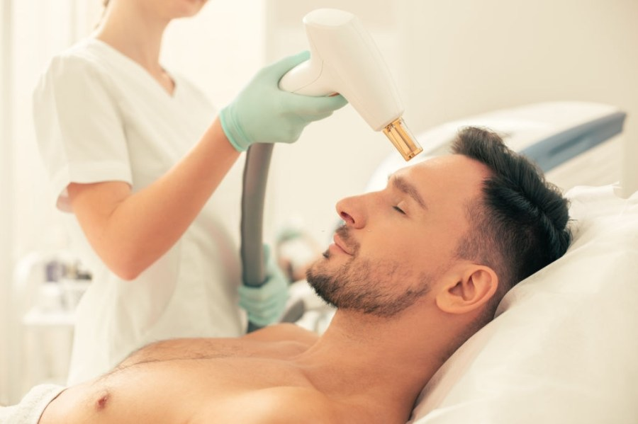 Microdermabrasion for Men: Everything You Need To Know  Close up of a shirtless man lying with his eyes closed and having laser stretch mark removal procedure on his forehead