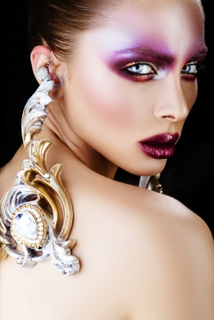 brunette woman in long earrings. high school model with creative make-up