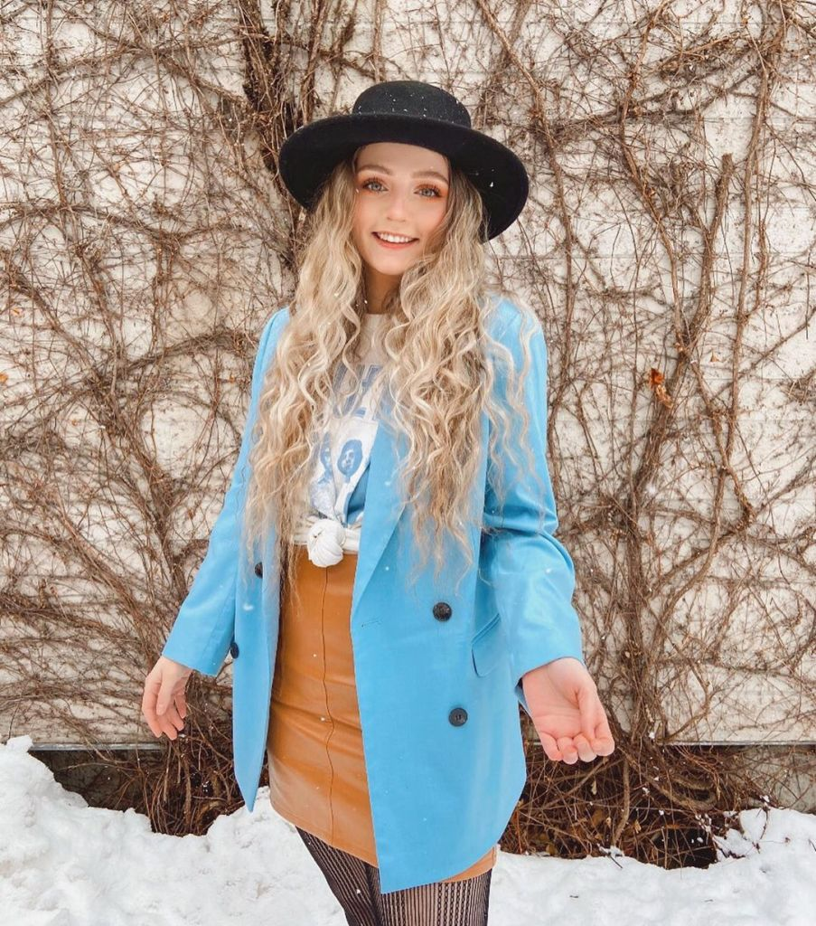 Girl standing in the snow wearing light blue blazer styled with a hat and stockings for the winter