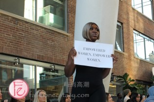 "model holding "" Empowered Women, Empower Women"" sign at Run The World 2019 event Fashion Show & Night Market"