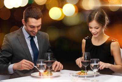 restaurant, couple and holiday concept - smiling couple eating main course with red wine at restaurant