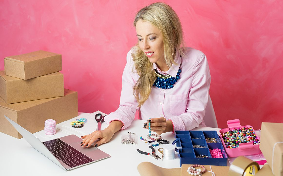 Woman working from home. Making pieces of jewellery and sells them on computer