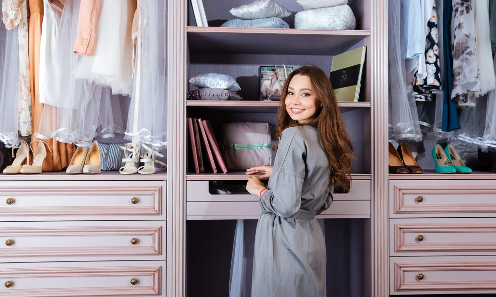 woman-standing-by-her-wardrobe-walk-in-closet-1000x600