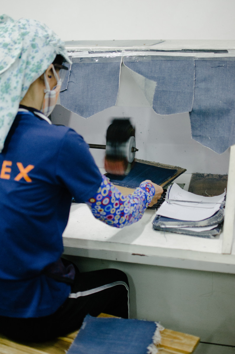 A Saitex employee individually distressing pieces of fabric that will become pockets. Photo: Whitney Bauck/Fashionista
