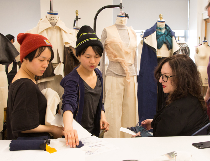 Sophie Theallet looks at a garment design with two students