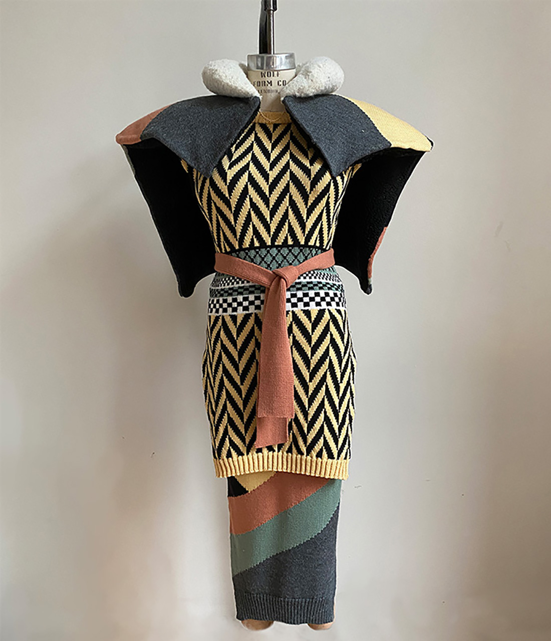 Multicolor geometric intarsia capelet over matching skirt and multicolor float jacquard tunic.