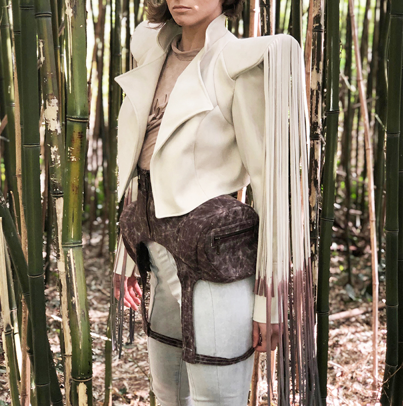 Jacket with structured shoulders and fringe worn with hip pocket harness and manipulated suede top