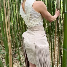 Woven fluting from front meets to weave again in back with stand up collar.