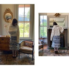 Ivory cable hand knit pullover with zip collar over a-line skirt with tiered fringe.