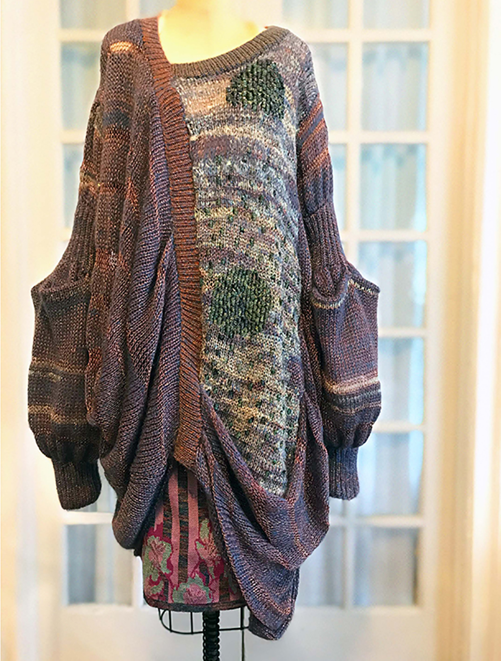 Iridescent pinks hand loomed side cowl and intarsia tunic over multicolor floral jacquard skirt.