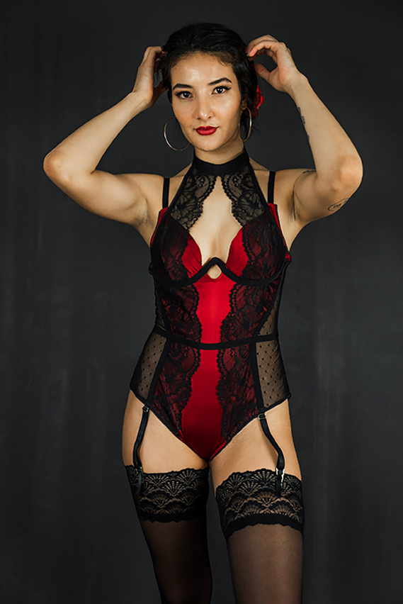 A half body front view of the red and black keyhole neckline bodysuit detailed with a high-neck lace overlay. Styled with garters attached to lace thigh highs.