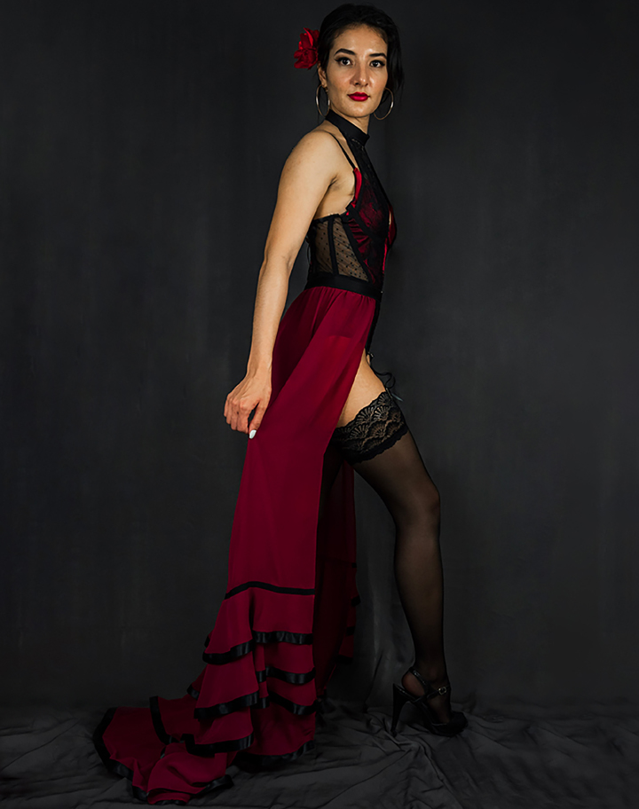 A full side view of the red and black bodysuit and ruffled skirt with train. Styled with garters attached to lace thigh highs and a red rose hairpiece.