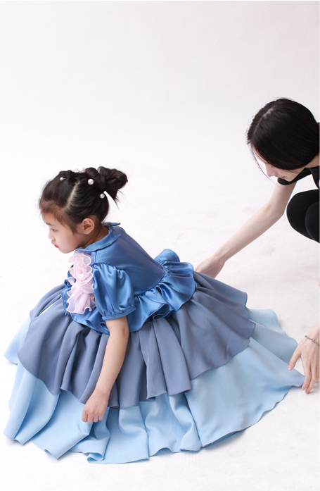 Little girl is sitting on the floor. Photo taken from the side. The designer is behind the model and is straightening the dress skirt.