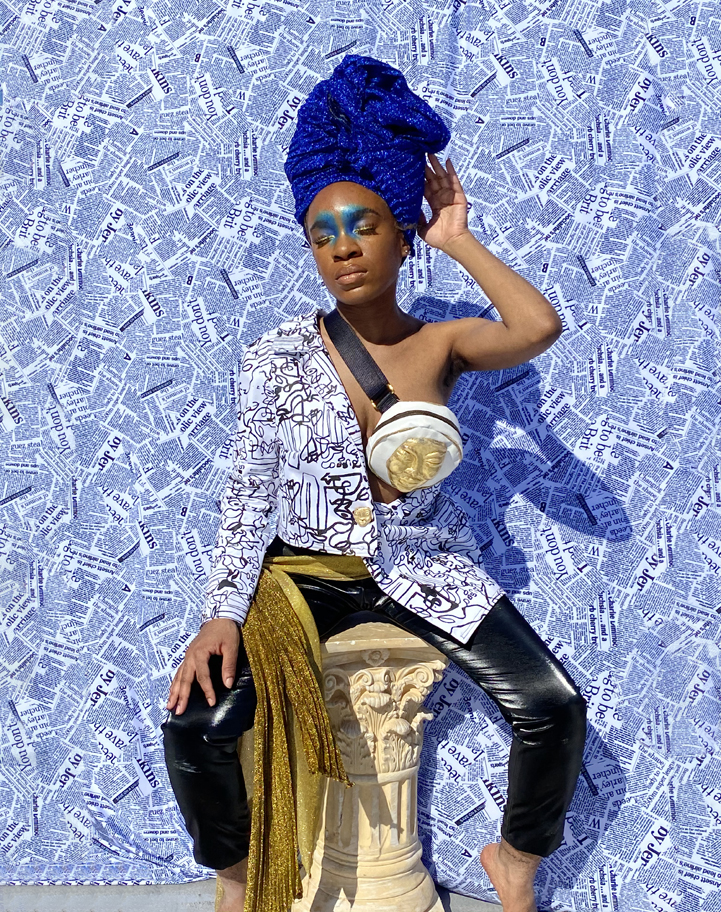 Woman seated on a column in shimmer blue head wrap. Eyes closed with face tilted upward toward sunlight. Abstract black and white print asymmetrical blazer. Black faux leather pants with golden glitter waist sash. Newsprint backdrop. Golden mask fanny pack accessory. Dramatic blue eyeshadow on inner eyelid and inner eyebrows.
