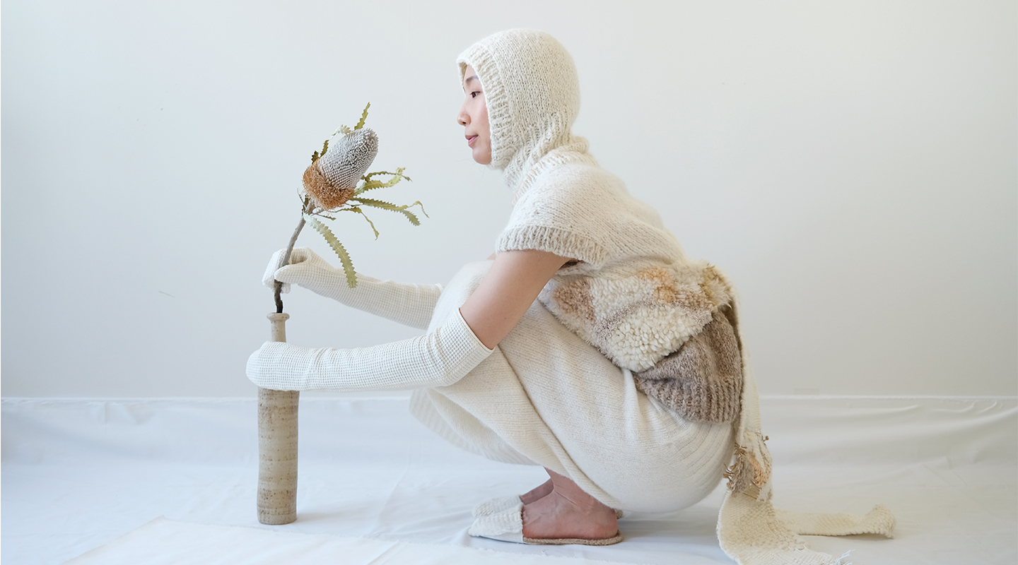 A color blocked sleeveless top, a white skirt, a latch hook vest, weaving straps, a white balaclava, white woven mittens, and sleepers
