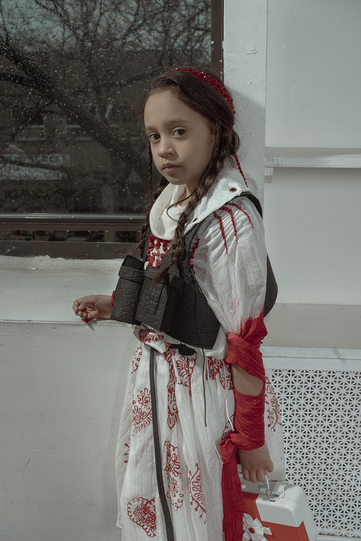 An eight-year-old brown hair girl holding a first-aid box, wearing a turtle neck white silky blouse, a red heart pattern printed box pleat skirt and a black vest, standing aside of a rainy window.