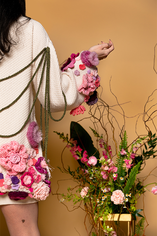 Back view of right side. Right arm extended, showing sleeve embellished with yarn flowers in shades of pink. Back right body is embellished with pink, purple, and magenta yarn flowers. Green knitted cords hang between the shoulders.