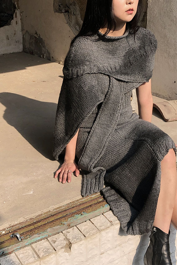 An asymmetrical layered hand knit cape, with ebony black dyeing that is inspired by demolished buildings.