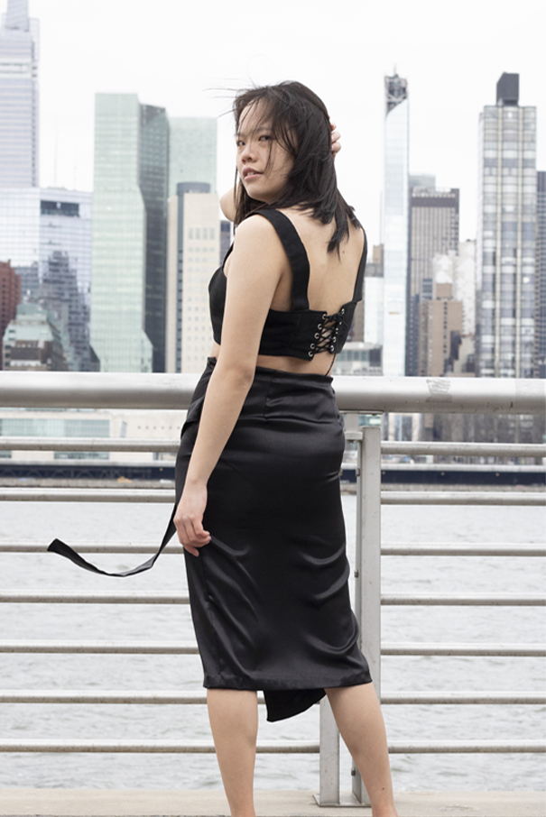 Sleeveless black cropped top with straps, corset closure on center back, and silver grommets and black suede cord trim application. Back of the black crepe, back satin midi wrap skirt, shows the two back darts and has an invisible side zipper closure.