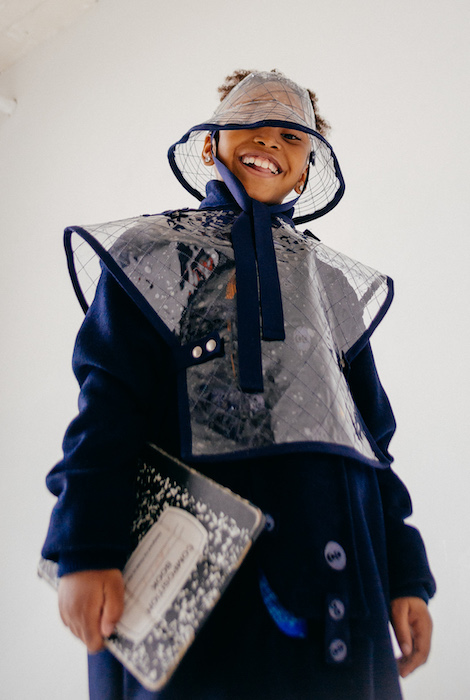 Above is a patched wool navy trench coat with button details. Layered on top is a quilted vinyl poncho and quilted vinyl bucket visor.