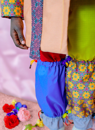 A closer look at the garments shows the toggles which make the pants adjustable to fit many sizes. Also shown is a detailed look at the geometric patterns.