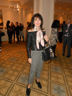 Betsy Cherkasky is wearing a classic leather top with pants by Worth. Her scarf is Hermes, her bag is by Fendi and her shoes are made by Aquatalia.