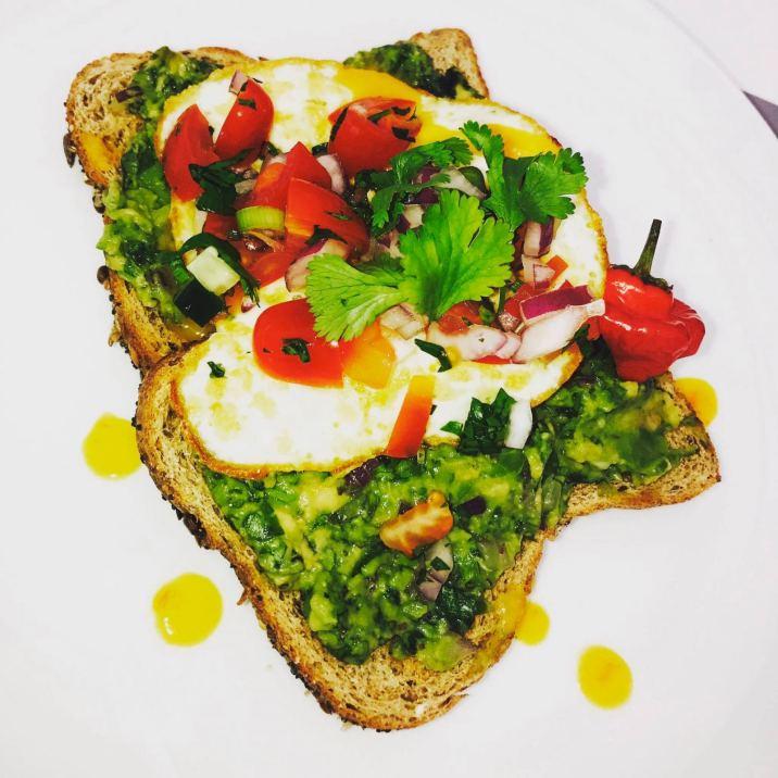 Zabuca choka topped toast with fried egg topped with fresh tomato choka and pepper sauce