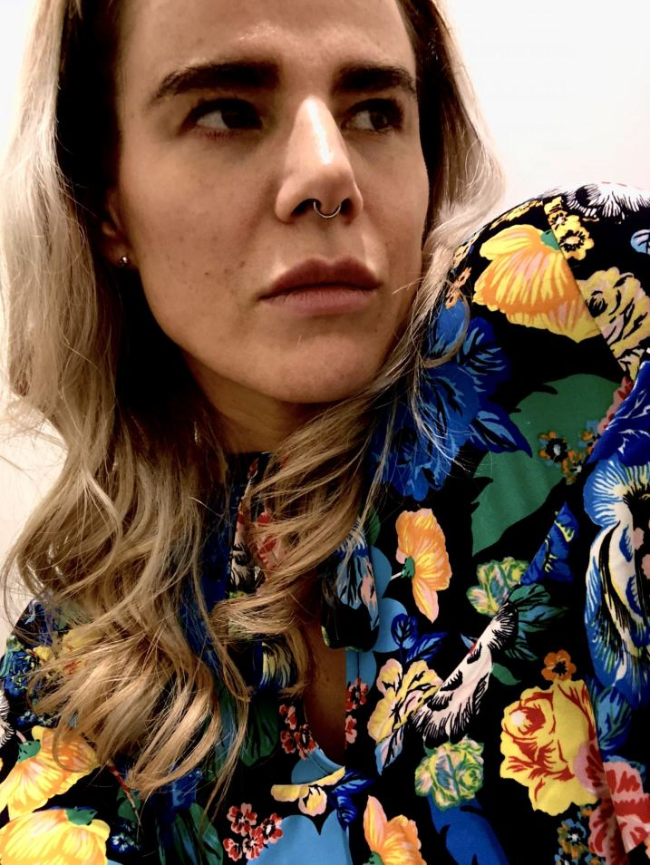 Close up of Pixie looking sideways in a floral dress with loosely curled hair by SHOW DRY Notting hill for London Fashion Week