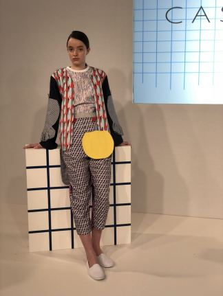 Cassey Gan FW18 London fashion Week A full length image of a model wearing separates: trousers, tee and jacket all with juxtaposed textures and prints with a yellow bag