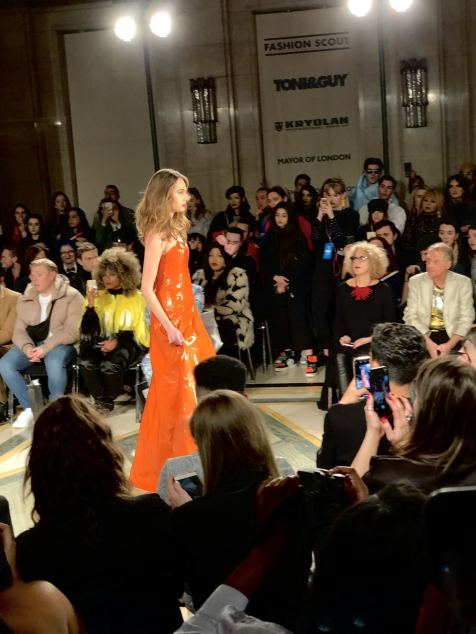 Malan Breton FW18 Fashion Scout London Fashion Week a model wearing an orange leather gown on the runway