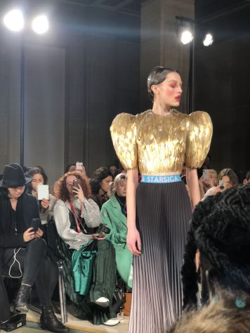 STARSICA FW18 LONDON FASHION WEEK a model in a guilded gold wing top on the runway to appear like wings