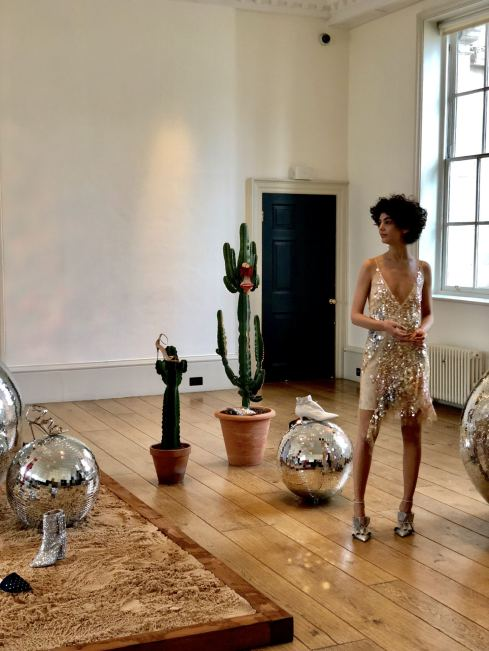 Alexander White FW18 Presentation London Fashion Week a shot showing a cactus, disco ball and a model showcasing silver shoes