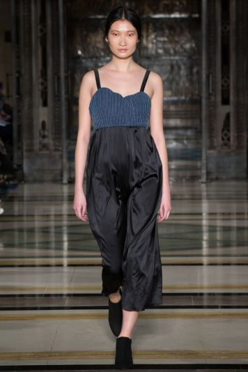 A model wears a denim and satin jumpsuit on the runway for SOE Jakarta at london Fashion Week FW18