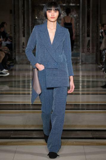 A model wears a denim pinstriped oversized pants suit on the runway for SOE Jakarta at london Fashion Week FW18