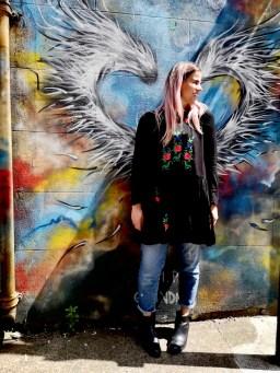 Street Art in Shoreditch: Pixie Tenenbaum posing in front of some street art angel wings