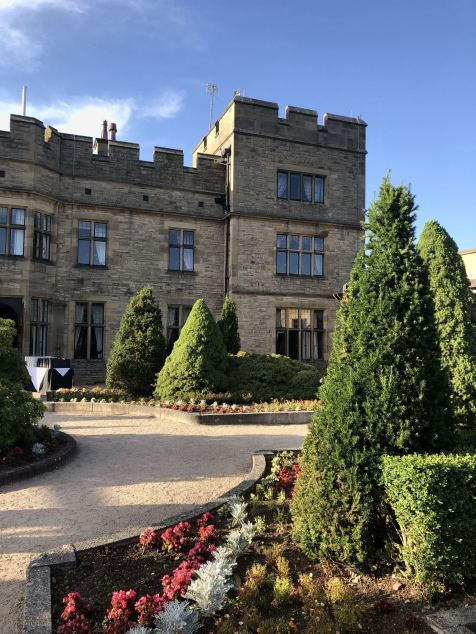 The rear of Slaley Hall in Northumberland, a view from the garden with blue skies overhead
