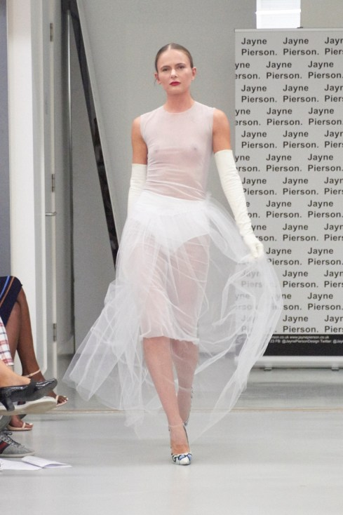 A model on the runway for Jayne Pierson SS19 at London Fashion Week Conde Naste College of Fashion and Design wearing a tulle dress, tight fitting at the top then opening out at the bottom to volumes of tulle, white high waisted panties are shown underneath (fashion voyeur blog)