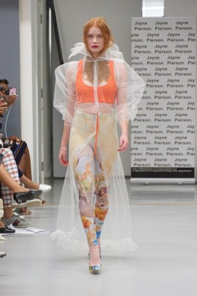 A model on the runway for Jayne Pierson SS19 at London Fashion Week Conde Naste College of Fashion and Design wearing a floor length white tulle overcoat with high nect and painted leggings underneath with an orange scoop neck vest (fashion voyeur blog)