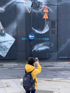 iPhone XS Camera Trial: A child using the iPhone XS on a photowalk around Shoreditch to photograph a huge street art mural covering an entire wall