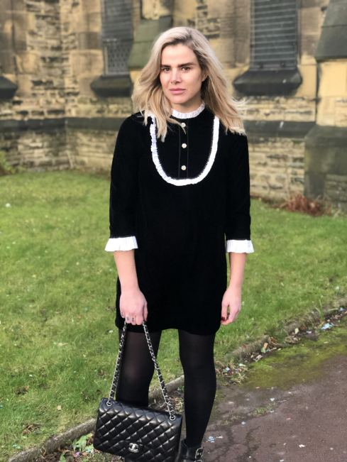 An image of Blogger Pixie Tenenbaum walking in a church yard wearing a black velvet mini dress in the style of The Weird Sisters with white detailing and glass buttons, carrying a Chanel quilted bag