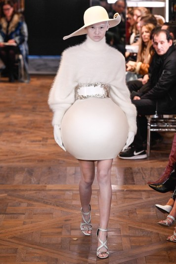 An image of a runway model at the Balmain couture Spring 2019 show wearing a huge cream outfit with bubble hem skirt