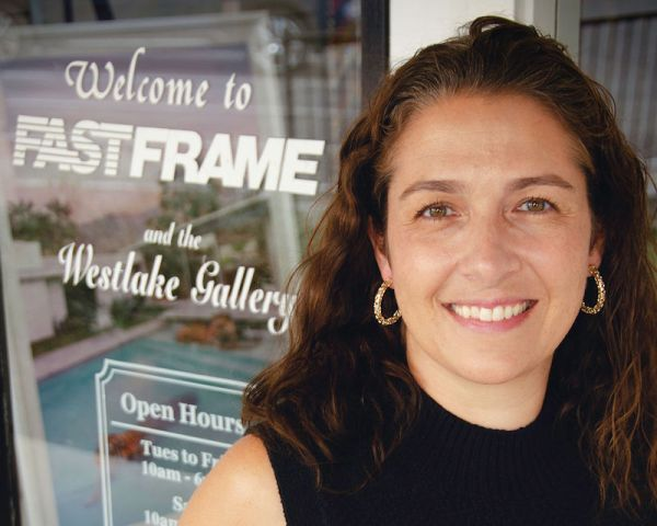 custom picture frame shop owner in front of store sign
