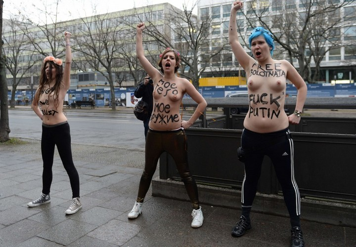 """Three topless Femen activists demonstrate in front of the Russian Embassy in Berlin on February 7, 2014. Femen staged the protest on the opening day of the Olympic Games in Sochi to demonstrate against Russian President Vladimir Putin's """"dictatorship and oppression of human rights in Russia"""". AFP PHOTO / PATRIK STOLLARZ"""